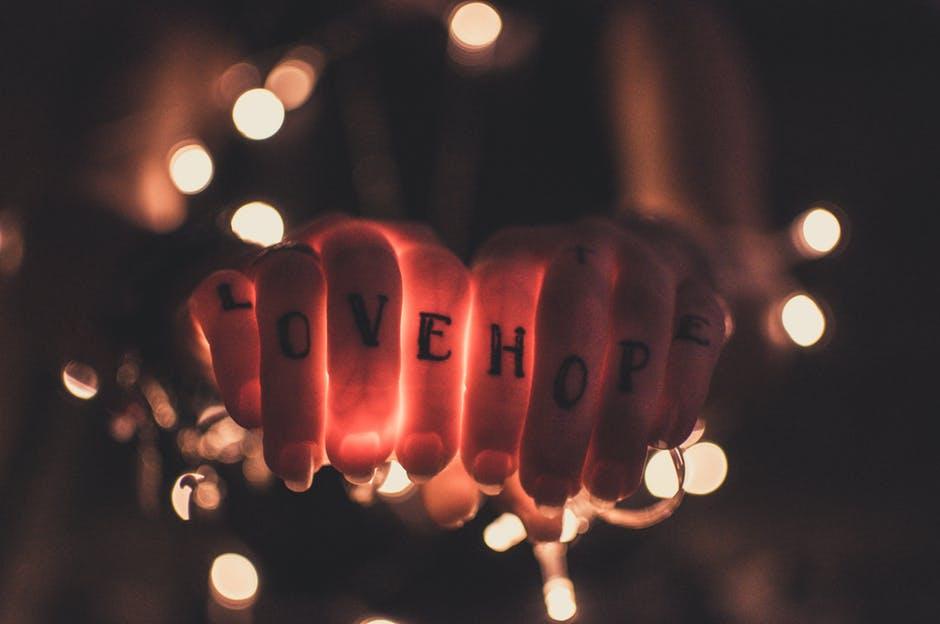 Selbstliebe lernen Zwei Hände mit Love und Hope