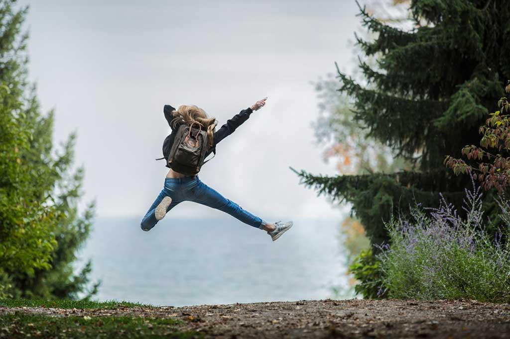 Selbstmitgefühl kann sich positiv auswirken, Frau springt freudig