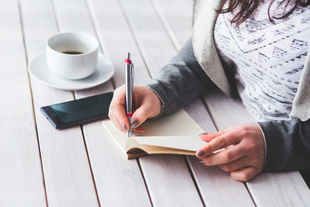 Frau schreibt Selbstmitgefühl Übung auf